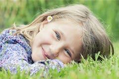 说谎在草微笑的女孩 免版税库存图片