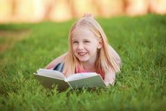 说谎在草的一个幼儿读书 免版税库存图片