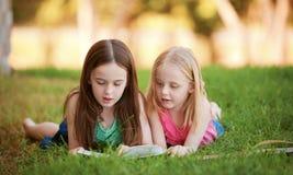 说谎在草的两个女孩户外读书。 库存图片