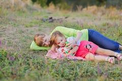 说谎在草的女儿和母亲 库存照片