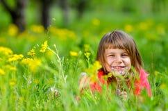 说谎在草的小女孩在春天 库存照片