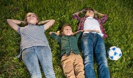 说谎在草的小组愉快的孩子 库存图片