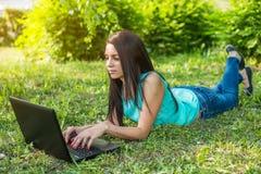 说谎在草的少妇,使用膝上型计算机和键入 免版税库存图片
