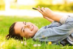 说谎在草的微笑的女孩 免版税库存照片
