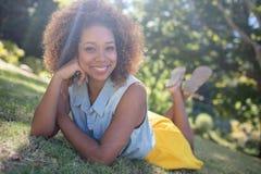说谎在草的微笑的妇女 免版税库存照片