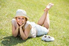 说谎在草的微笑的少妇 免版税库存图片