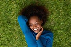 说谎在草的微笑的非洲妇女 免版税库存图片