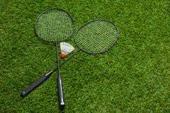 说谎在草的横渡的羽毛球拍 免版税库存照片