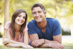 说谎在草的浪漫夫妇在夏天公园 免版税库存图片