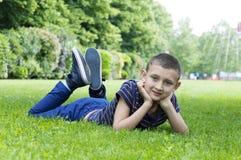 说谎在草的男孩在公园 免版税库存照片