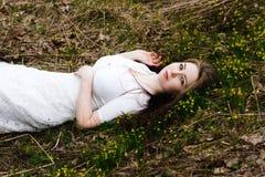 说谎在草的白色礼服的美丽的无辜的妇女 免版税库存照片