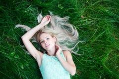 说谎在草的蓝色礼服的少妇 库存图片