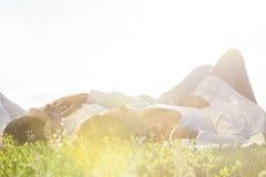 说谎在草的年轻夫妇反对清楚的天空 库存图片