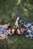 说谎在草的年轻夫妇微笑对照相机 免版税库存图片