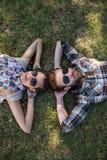 说谎在草的年轻夫妇微笑对照相机 免版税库存照片