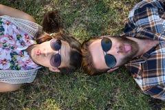 说谎在草的年轻夫妇微笑对照相机 库存照片