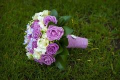 说谎在草的紫色和白玫瑰婚礼花束  免版税库存照片