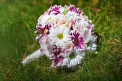 说谎在草的紫色和白花婚礼花束  免版税库存照片