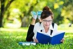 说谎在草阅读书的微笑的偶然学生 免版税图库摄影