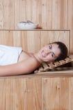 说谎在蒸汽浴里面的愉快的妇女 免版税库存图片