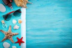 说谎在蓝色木背景的海星、小卵石和壳 有标签的一个地方 库存图片