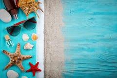 说谎在蓝色木背景的海星、小卵石和壳 有标签的一个地方 免版税库存照片