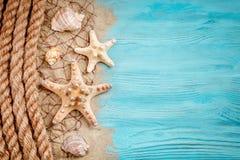 说谎在蓝色木背景的海星、小卵石和壳 有标签的一个地方 图库摄影