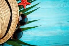 说谎在蓝色木背景的海星和棕榈叶 有标签的一个地方 库存图片