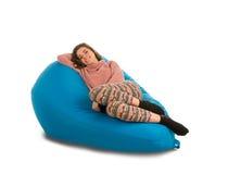 说谎在蓝色装豆子小布袋沙发的美丽的少妇 库存照片