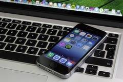 说谎在视网膜macbook赞成键盘的IPhone 5s 免版税库存照片