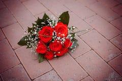 说谎在路的红色玫瑰美丽的花束 免版税库存照片