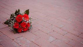 说谎在路的红色玫瑰美丽的花束 免版税库存图片