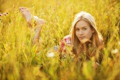 说谎在野花中的愉快的女孩 免版税库存图片