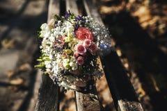 说谎在长凳的美丽的新娘花束 免版税库存图片