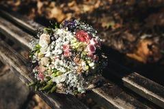 说谎在长凳的美丽的新娘花束 免版税库存照片