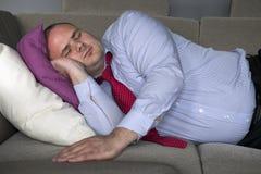 说谎在长沙发和睡眠的商人 免版税库存图片