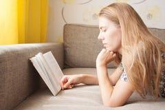 说谎在长沙发和读书的美丽的逗人喜爱的女孩 免版税图库摄影