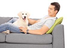 年轻说谎在长沙发的人和小狗 免版税库存照片