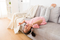 说谎在长沙发的愉快的小女孩 库存图片