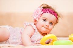 说谎在长沙发的桃红色礼服的小女孩 库存照片