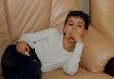 说谎在长沙发的男孩的画象 库存照片