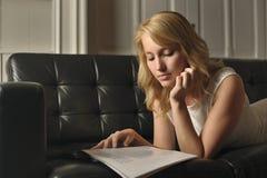 说谎在长沙发读书的白肤金发的妇女 库存图片