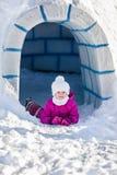说谎在雪的小女孩在入口附近对园屋顶的小屋 库存图片
