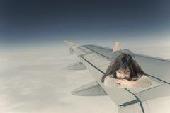 说谎在面对照相机的航空器的翼的小女孩 免版税库存图片