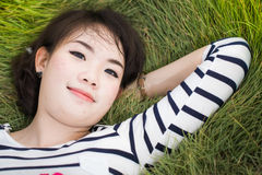 说谎在领域的春天亚裔妇女。 免版税库存图片