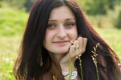 说谎在领域的美丽的微笑的女孩 免版税图库摄影