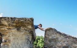 说谎在高砂岩岩层顶部的妇女说谎在边缘 库存照片
