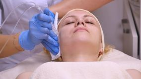 说谎在临床桌上的年轻美丽的妇女,美容师做她面部电镀物品刺激按摩 股票视频