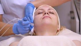 说谎在临床桌上的年轻美丽的妇女,美容师做她面部电镀物品刺激按摩 影视素材