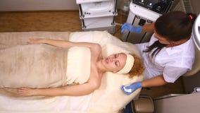 说谎在临床桌上的年轻美丽的妇女,美容师做她面部电镀物品刺激按摩 股票录像